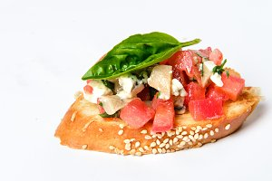 Bruschetta with cheese Feta, basil and meat pieces
