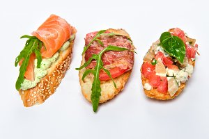 Three different bruschettes with greens, cheese, meat and fish