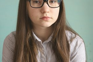 teen girl in glasses with long brown hair