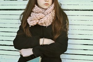 teenager girl in glasses with long brown hair and book