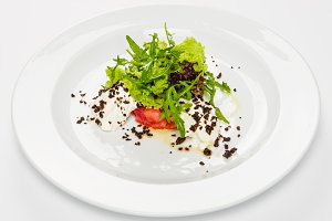 Vegetable salad with white sauce and grilled crumbs on plate.