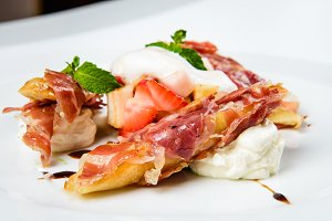 Baguette pieces covered with grilled bacon on plate served luxury.