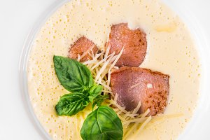Cream soup with basil, meat steak and cheese on plate.
