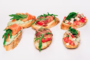 Six bruschettes with greens, cheese, meat and fish