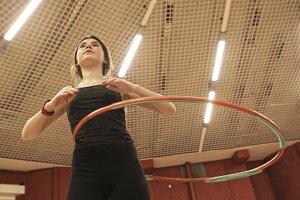 teenager girl with hula hoop in gym