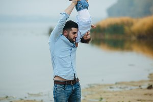 Dad holding infant son by his feet