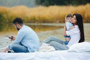 Happy young family relaxing together on the lake