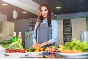 Pretty female chef standing, cooking , posing, looking at camera with fruit and vegetables on table.