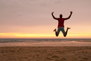 Young man jumping at the beach