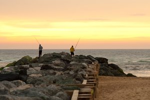Men fishing at the beach at sunset