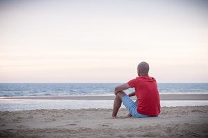 Young man sitting in the beach sand