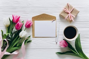 Cup of coffee with gift and tulips.