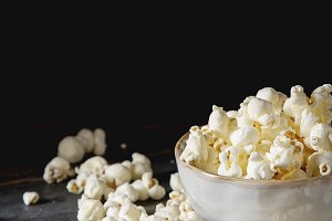 Salted popcorn in a cup. Dark background. Selective focus. Fast food for movies.