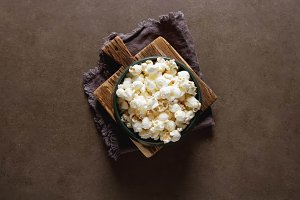 Salted popcorn in a cup. Dark background. Selective focus. Fast food for movies. Top view