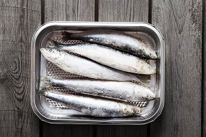 Frozen sardines. Cornish. For grill and BBG. Dark wooden background.