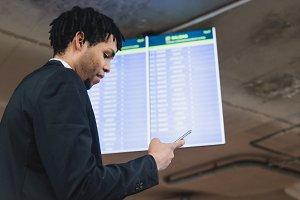 Man browsing phone near schedule