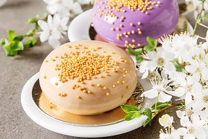 Fashionable mousse cake with a mirror glaze decorated with spring flowers. Dark background