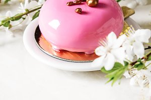Fashionable mousse cake with a mirror glaze decorated with spring flowers. Light white background.