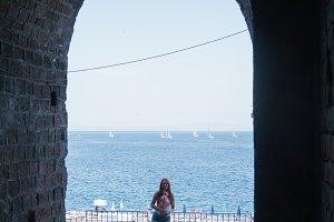 Young attractive female posing near sea mainsail, sorrento, Italy