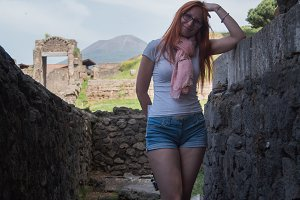 Beautiful red hair woman in glasses and shorts standing in pompeii, Italy - hot summer midday