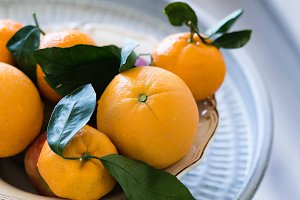 Oranges in bowl placed on metal tray