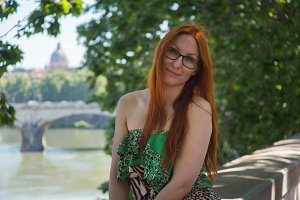Beautiful red hair girl in glasses posing in street of Rome, Italy
