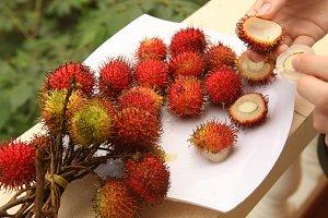 rambutan berries with hands peeling
