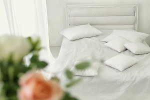 white bed in beddrom with pillows close up photo
