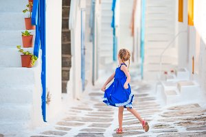 Little girl in blue dress outdoors. Kid dancing at street of typical greek traditional village on Mykonos