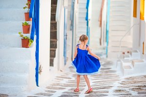 Beautiful girl at street of typical greek traditional village with amazing steps and white walls on Mykonos