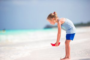 Adorable little girl during beach vacation having fun in shallow water
