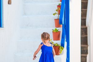 Cute girl in blue dress at street of greek village on Mykonos Island, in Greece
