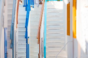 Colorful stairs on old narrow streets of greek island. Beautiful architecture building exterior with cycladic style.