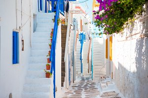 Traditional houses with blue doors and stairs in the narrow streets of greek village