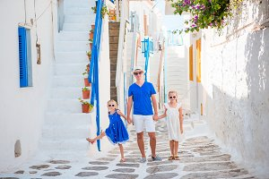 Father and kids at street of greek traditional village on Mykonos Island