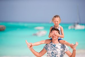 Happy father and his little daughter at tropical beach having fun