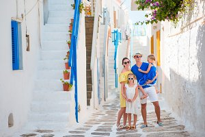 Family vacation in small old greek town. Parents and kids at street of greek traditional village on Mykonos Island