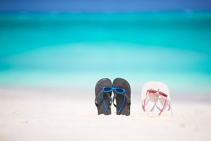 Summer flip flops with sunglasses on white beach. Closeup beach accessories.