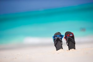 Summer black flip flops with sunglasses on white beach