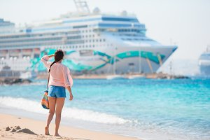 Young beautiful girl on the beach background big cruise ship.