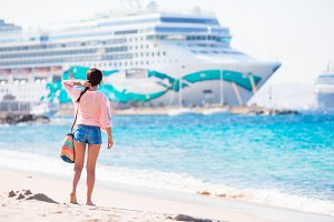 Young beautiful woman on the beach background big cruise ship.