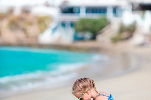 Adorable little girl have fun at tropical beach on simmer vacation