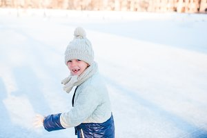 Adorable little girl going skate in winter snow day outdoors