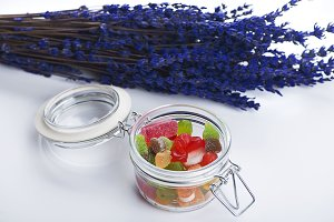 Blue flower next to a jar full of chucerías on white background