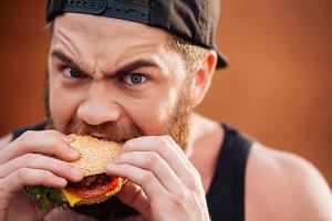 Angry irritated young man eating hamburger outdoors