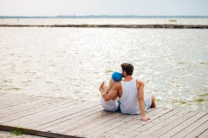 Loving couple on the beach hugging while looking at sea