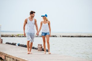 Romantic young beautiful couple walking on the beach holding hands