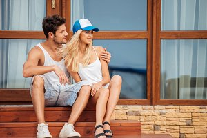 Young beautiful couple sitting on house steps outdoors