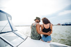 Beautiful loving young couple sitting and hugging on yacht