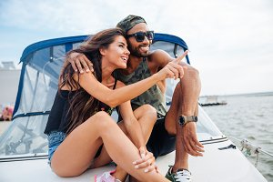 Couple hugging and pointing away on boat